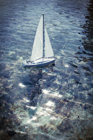 Toy boat sailing on a pond. Backlight photo. photo