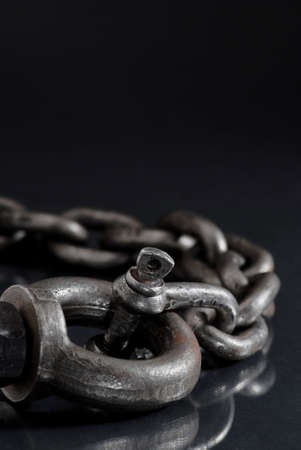 Old weathered industrial chain with ring clamp.