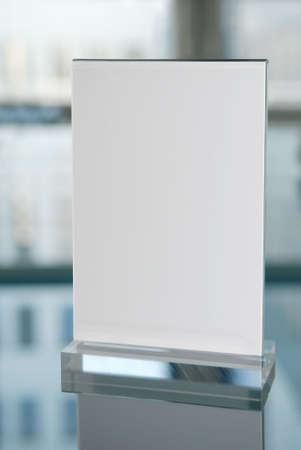 Plexiglass information board on glasstable with reflection of a  building. Reklamní fotografie