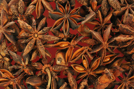 dozens: Star-Anise Background with dozens of stars on red background. Stock Photo