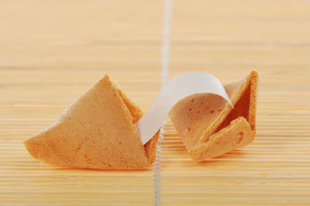Broken fortune cookie with text banner on rattan background. Stock Photo - 4036397