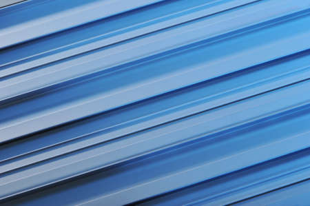 routed: abstract background made of aluminum sectional strips in blue light Stock Photo