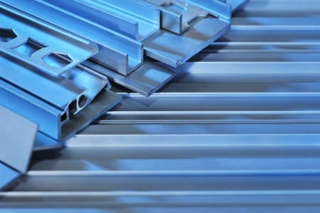routed: many different aluminum sectional strips in blue light Stock Photo