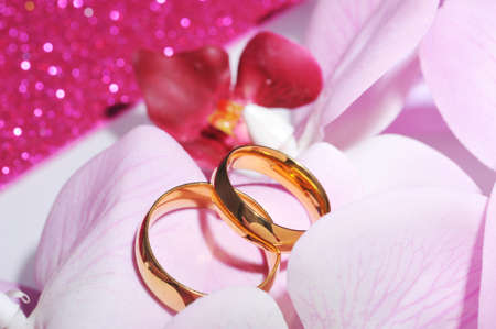 cordiality: Two golden rings in pink orchis on pink glitter background Stock Photo