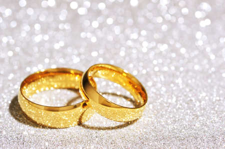 cordiality: Two golden rings on white glitter background