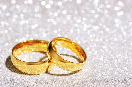 Two golden rings on white glitter background
