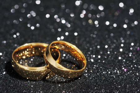 cordiality: Two golden rings on black glitter background Stock Photo