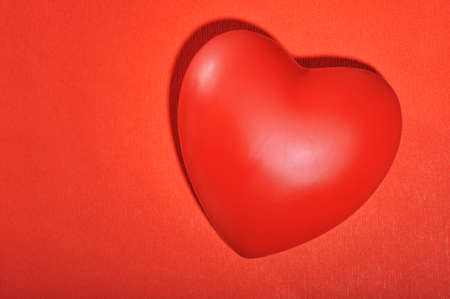 cordiality: Red heart on red paper structure  background