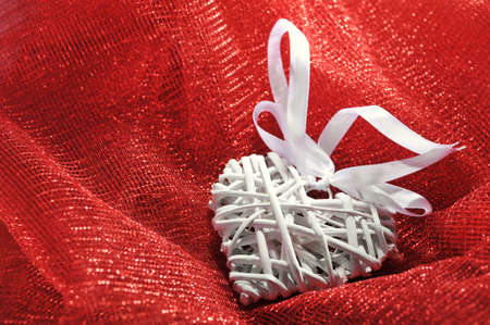 cordiality: white wooden rattan heart on red sparkle cloth