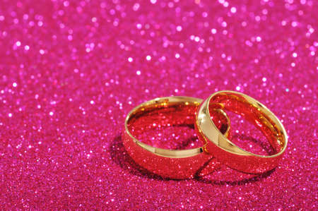 cordiality: Two golden rings on pink glitter background