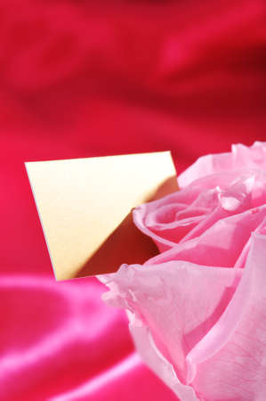 cordiality: Pink rose with golden greeting card on red satin background Stock Photo