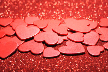 mother'sday: many small red wood hearts on red sparkle background Stock Photo
