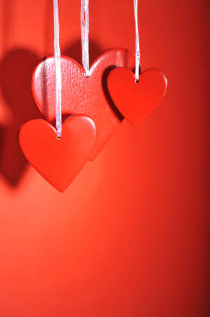 three red wood hearts in front of red background