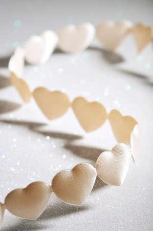 cordiality: chain of white-yellow textilehearts on silver sparkle background Stock Photo