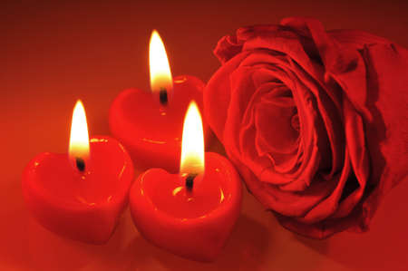 cordiality: three luminous candlehearts with red rose Stock Photo