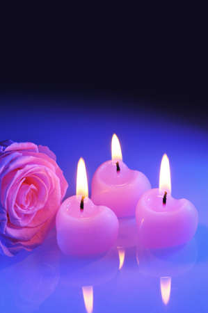 mother'sday: three luminous pink candlehearts with pink rose in blue light Stock Photo