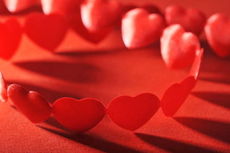 chain of small red textilehearts on red background Stock Photo
