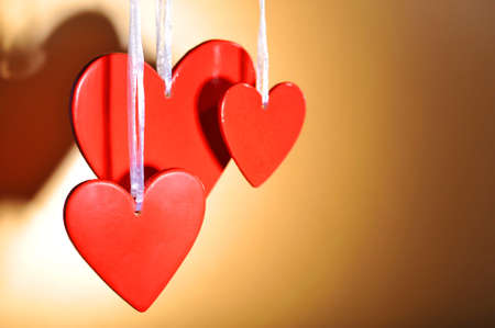 agradecimiento: tres corazones de madera de color rojo en frente de fondo dorado Foto de archivo