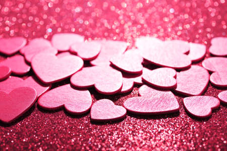 mother'sday: many small pink wood hearts on red sparkle background Stock Photo
