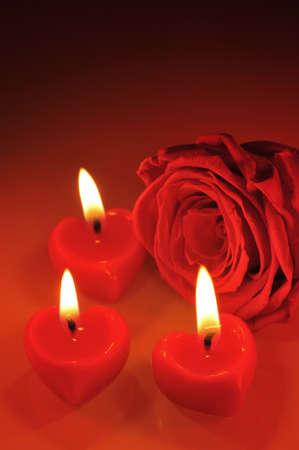 agradecimiento: tres candlehearts rojos luminosos con rosa roja Foto de archivo