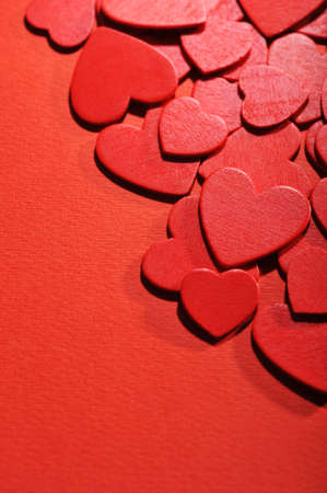 many small red wood hearts on red background