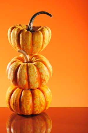 mirroring: three halloween pumpkins on orange mirroring background
