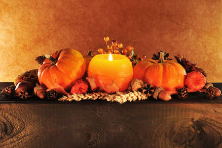 Thanksgiving - pumpkins in candle light on old weathered wooden boards in front of brown background Banco de Imagens