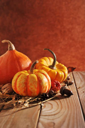 three pumpkins on old weathered wood grain with brown background with light from the side Banco de Imagens