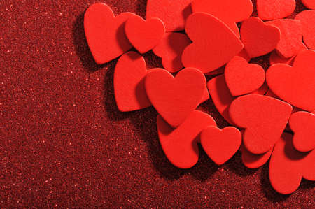 cordiality: many small red wood hearts on red sparkle background Stock Photo