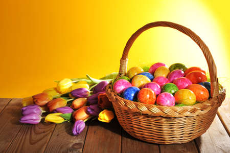 hen's: big easter nest with many colored hen? s eggs and tulips on wooden board Stock Photo