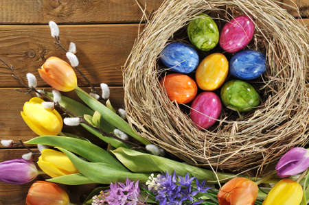 hen's: Easter nest with many colored hen?s eggs, tulip, hyacinth and pussy willow on old wooden board Stock Photo