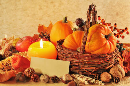 Thanksgiving - different pumpkins, nuts, maize cob and apple in rattan basket with candlelight and copyspace photo