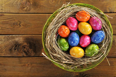 hen's: Easter basket with many colored hen? S eggs on old wooden board