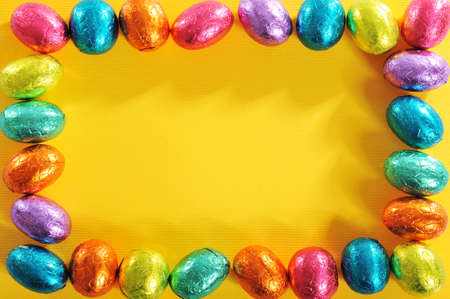 many colored: Many colored chocolate easter eggs as frame on yellow paper