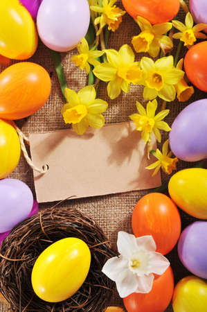 hen's: colorful easter eggs with narcissus on jute bag Stock Photo