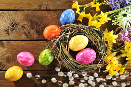 hen's: narcissus, easter eggs, easter basket and catkin on old weathered wooden board Stock Photo