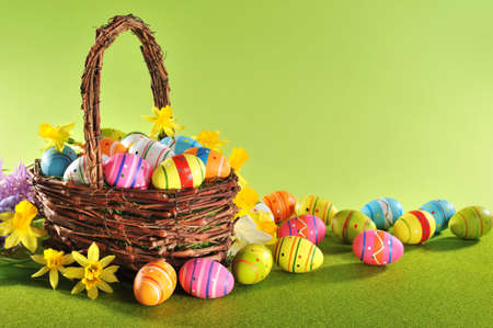五顏六色的複活節彩蛋和水仙在復活節巢在草地上
