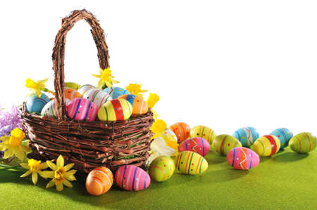 colorful easter eggs and narcissus in easter nest on grass Standard-Bild