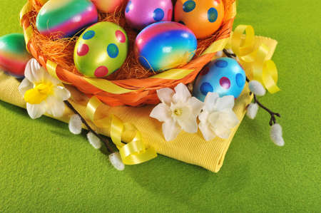 hen's: Colorful easter basket with painted easter eggs, narcissus and catkin
