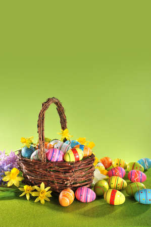 colorful easter eggs and narcissus in easter basket on grass