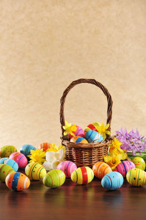 easter nest: many painted easter eggs with easter nest and hyacinth in front of brown background Stock Photo