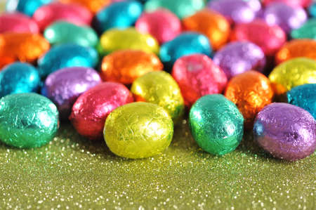 macro detail of many colored chocolate easter eggs on glitterbackground