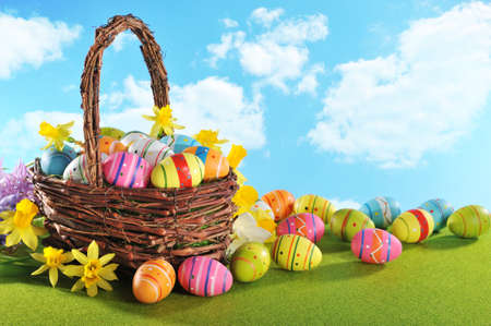 colorful easter eggs and narcissus in easternest on grass with sky Banco de Imagens