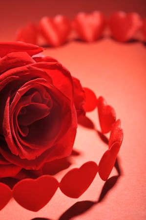 cordiality: chain of textile arts before with red rose on red background Stock Photo