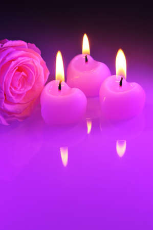 agradecimiento: three luminous pink candle hearts with pink rose in purple light Foto de archivo