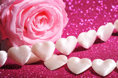 cordiality: chain of white textile arts before with pink rose on pink sparkle background Stock Photo