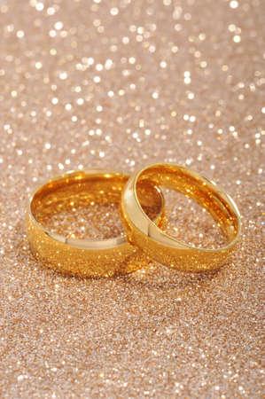 Two golden rings on gold glitter background
