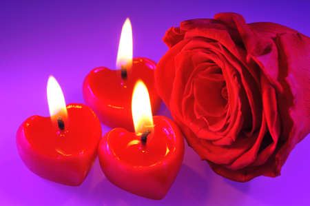 three luminous red candle hearts with red rose Stock Photo