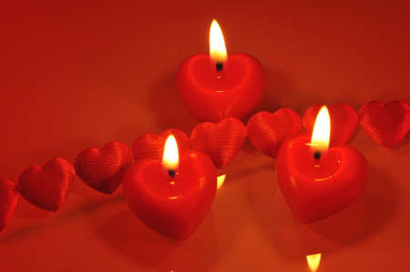 cordiality: three luminous red candle hearts with textile arts before Stock Photo