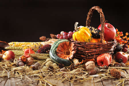 corn flower: pumpkin, pomegranate, apple, nuts, berries and grain with basket on old weathered wooden floor